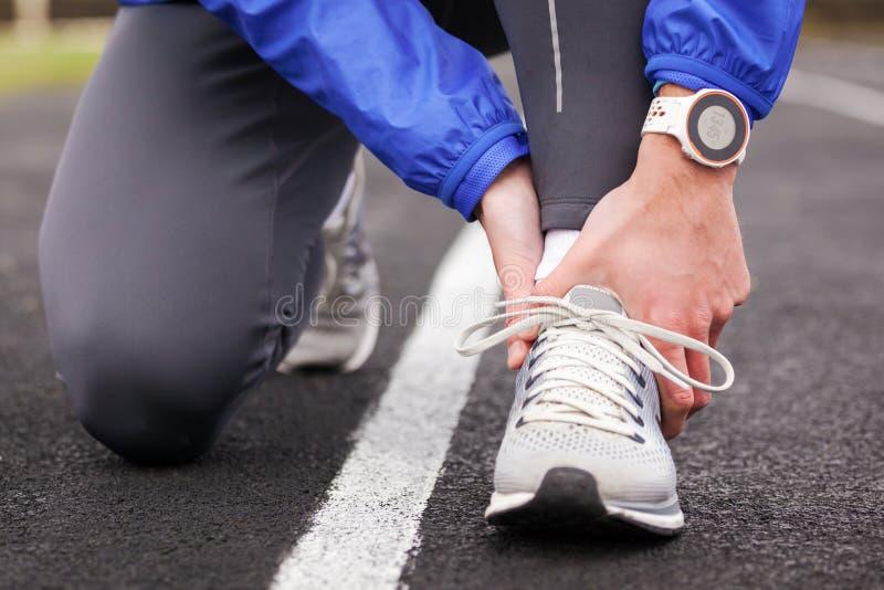 Colpo potato di un giovane che tiene la sua caviglia nella distorsione di dolore una f fotografia stock libera da diritti