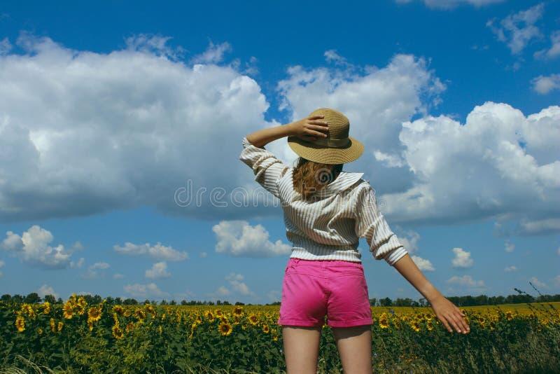 Colpo potato di una ragazza, portante un cappello e una camicia a strisce bianca, stante e guardante al lato sopra il fondo del c immagine stock libera da diritti