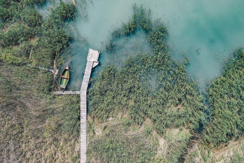 Colpo sopraelevato di un bacino di legno alla costa con un peschereccio accanto  immagini stock