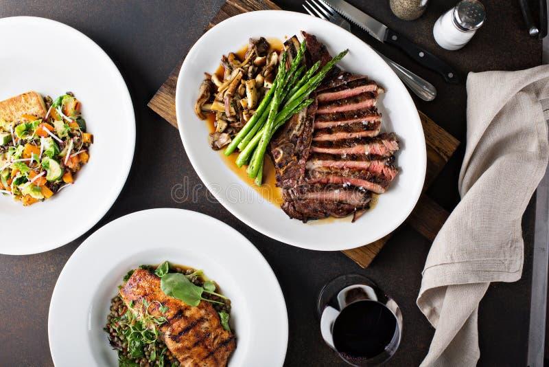 Colpo sopraelevato di una tavola di cena con bistecca ed il salmone immagini stock