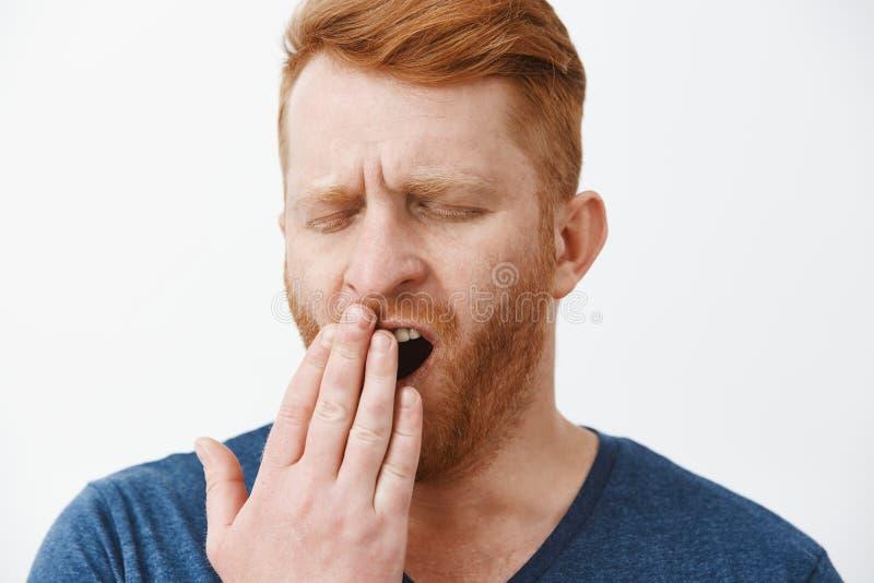 Colpo in testa dell'imprenditore maschio attraente stanco con capelli rossi e della barba, sbadigliando con gli occhi chiusi, cop fotografie stock libere da diritti