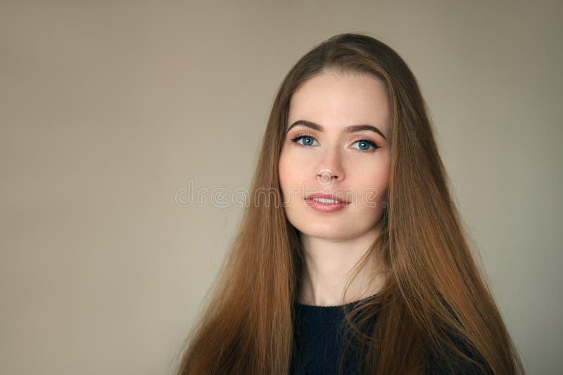 Colpo in testa dell'interno di bella donna sembrante naturale felice nel fondo blu scuro di beige del maglione immagini stock