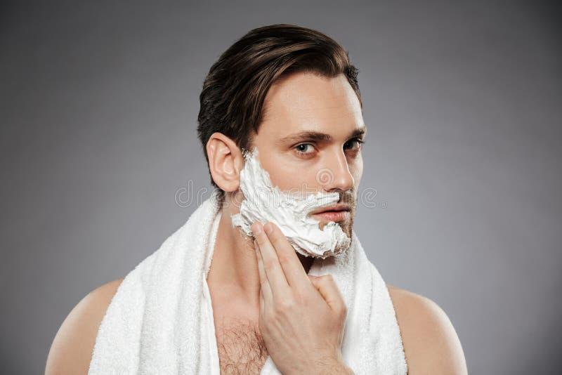 Colpo in testa dell'uomo bello concentrato che mette radendo schiuma sul fa immagine stock