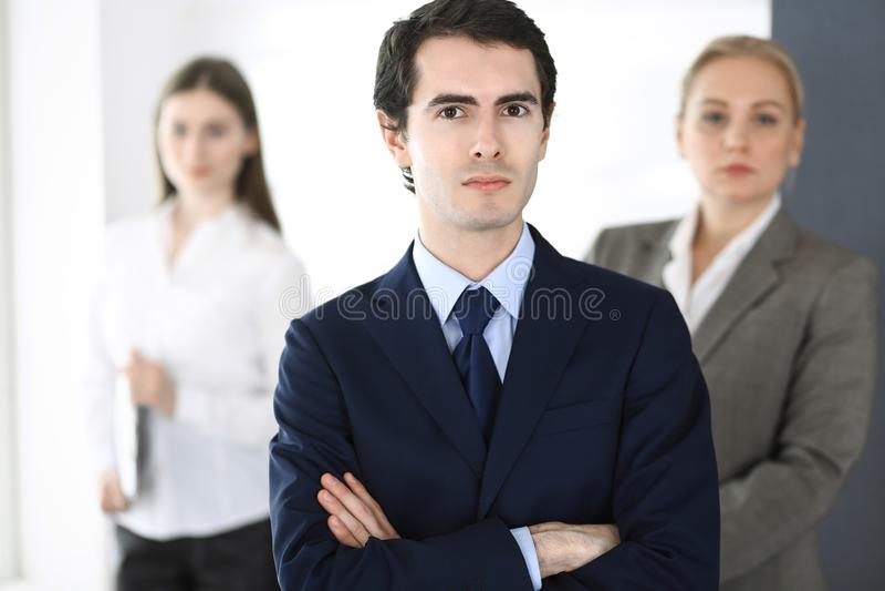 Colpo in testa dell'uomo d'affari che sta diritto con i colleghi al fondo in ufficio Gruppo di gente di affari di discussione fotografie stock
