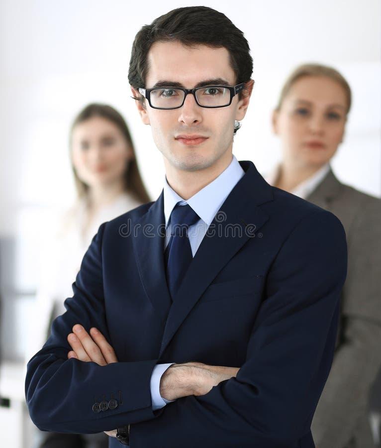 Colpo in testa dell'uomo d'affari che sta diritto con i colleghi al fondo in ufficio Gruppo di gente di affari di discussione fotografia stock libera da diritti