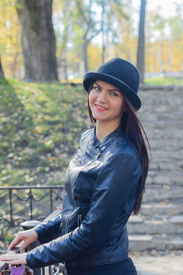 Colpo in testa della ragazza adulta con capelli marroni scuri diritti lunghi in cappello e bomber di giocatore di bocce neri immagini stock libere da diritti