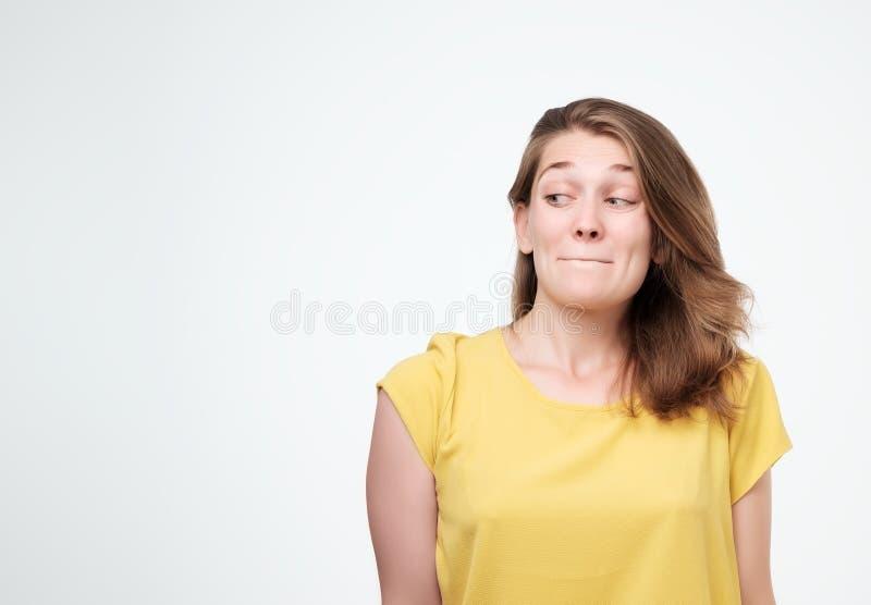 Colpo in testa di bella donna abila in maglietta gialla che guarda da parte rientrante per realizzare piano ingannevole immagine stock
