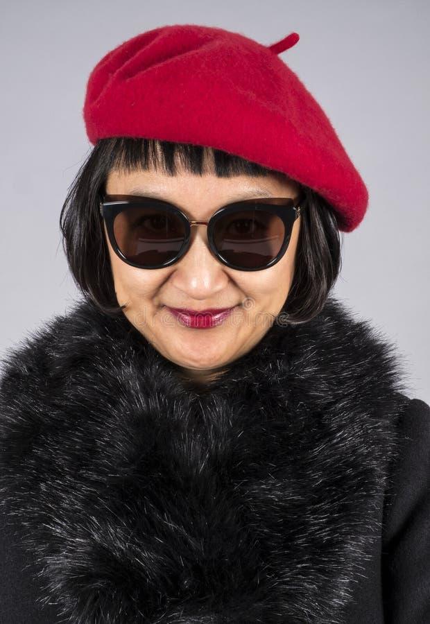 Colpo in testa di una donna asiatica con i capelli di scarsità che portano un berretto rosso fotografia stock