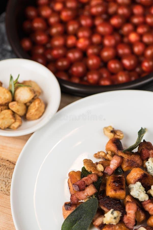 Colpo verticale del piatto con le foglie di verdure del manzo, del pollo e vicino ad un piatto laterale ed ai piccoli pomodori fotografia stock libera da diritti