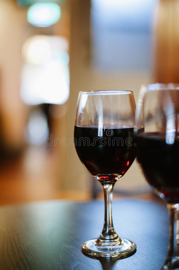 Colpo verticale del primo piano di un vetro di vino rosso scuro immagine stock libera da diritti