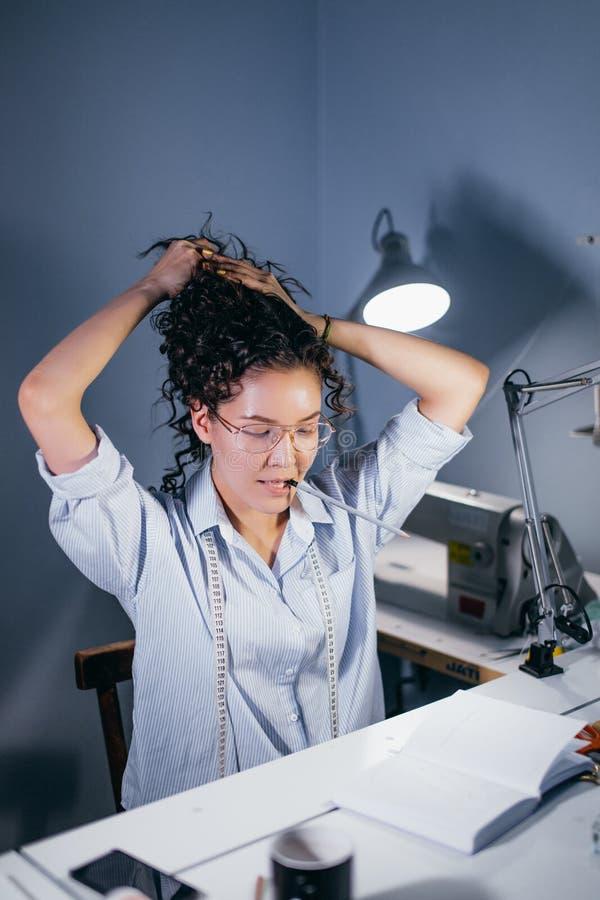 Colpo verticale della cucitrice che rimette capelli ondulati scuri immagine stock libera da diritti