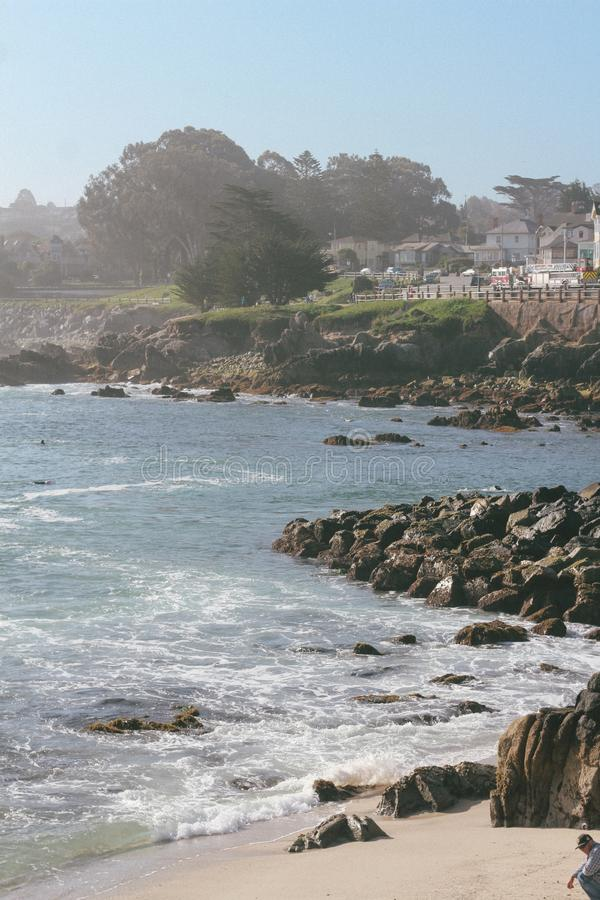 Colpo verticale delle onde del mare che colpiscono la riva e le rocce immagini stock