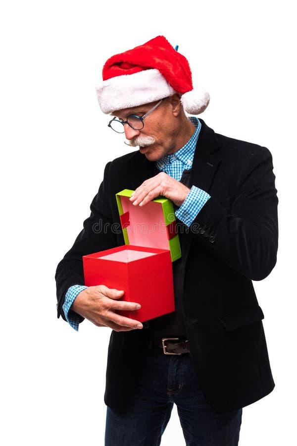 Colpo verticale di un anziano sorpreso che apre un regalo di Natale isolato su bianco immagini stock libere da diritti
