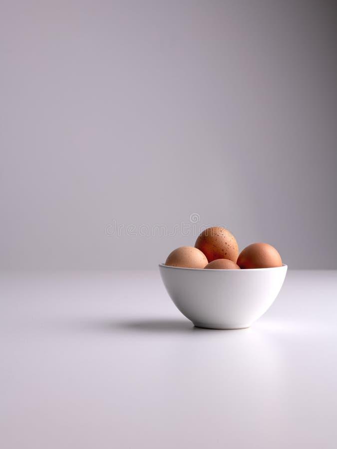 Colpo verticale di una ciotola bianca con le uova marroni in su una superficie bianca e su un fondo pulito grigio immagini stock libere da diritti