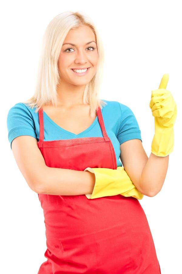 Colpo verticale di una donna delle pulizie che dà un pollice su fotografia stock