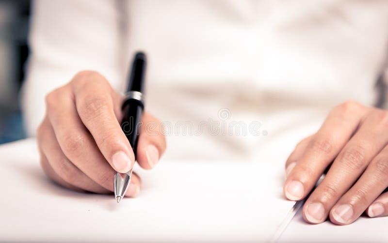 Colpo vicino di una scrittura umana della mano qualcosa sulla carta immagini stock libere da diritti