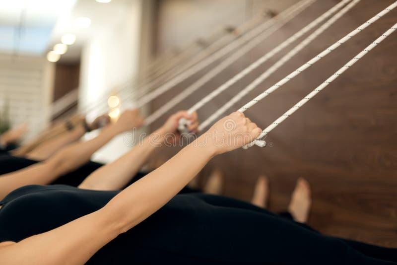 Colseup妇女手垂悬在晒衣绳平行的藏品绳索对在伸展线的地面实践的瑜伽在健身房 适合和 免版税库存照片