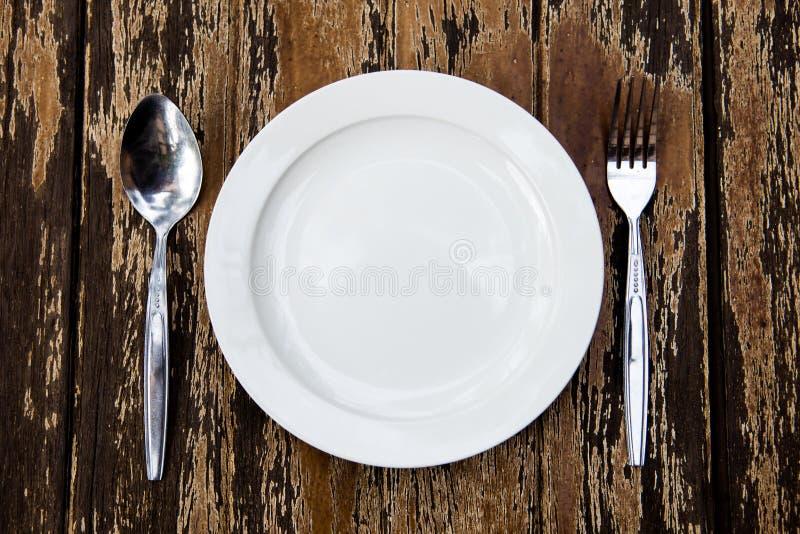 Coltelleria del piatto sul vecchio legno della tavola. fotografie stock