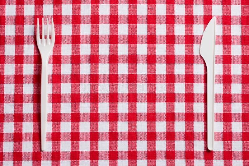 Coltelleria di plastica sulla tovaglia checkered immagini stock libere da diritti