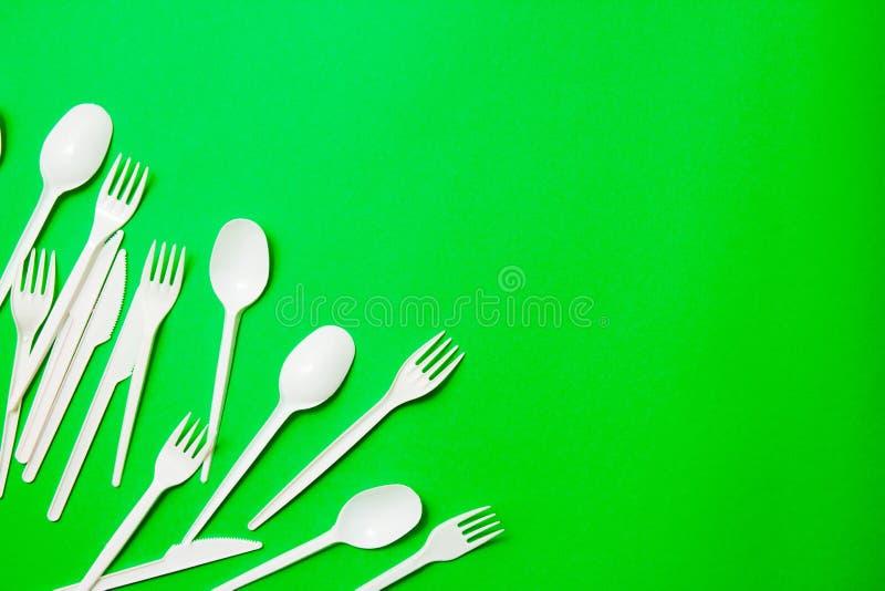 Coltelli di plastica monouso bianchi, cucchiai, forcelle su un fondo verde Dica no a plastica monouso Ambientale, inquinamento fotografia stock libera da diritti