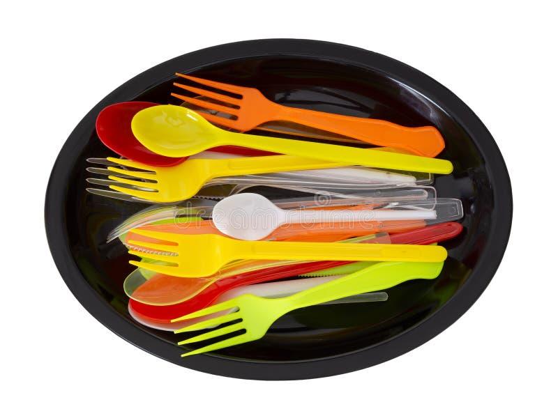 Coltelli, forchette e cucchiai di plastica sulla banda nera isolata su bianco immagine stock libera da diritti