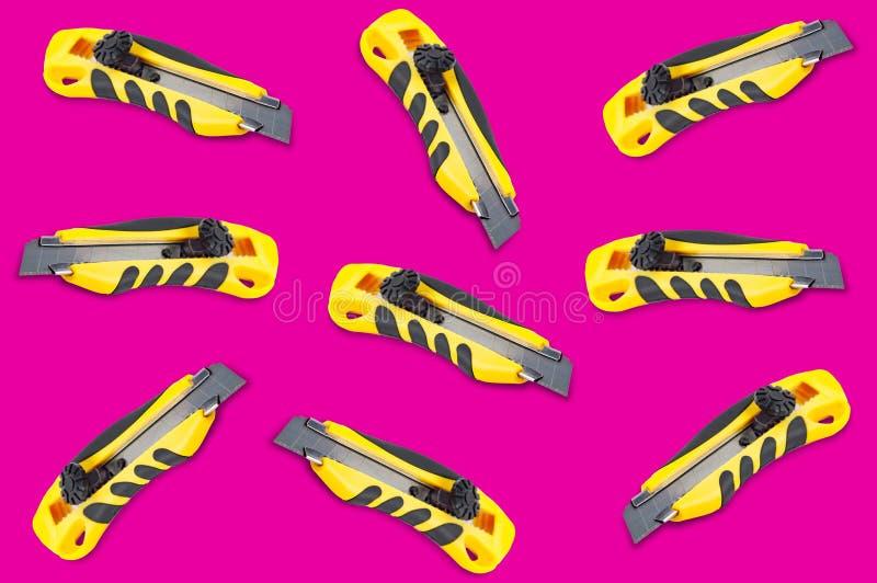 Coltelli sparsi della cancelleria con la maniglia di plastica gialla e nera su fondo rosa fotografia stock