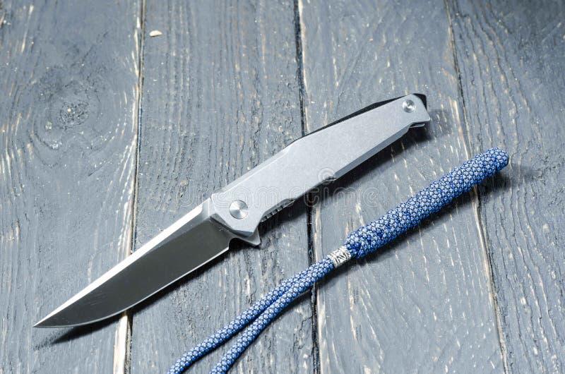 Coltello con una maniglia del metallo e una cordicella blu facciata frontale immagine stock libera da diritti