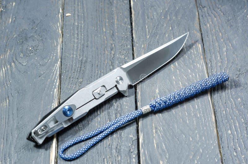 Coltello con una maniglia del metallo e una cordicella blu Lato posteriore immagini stock