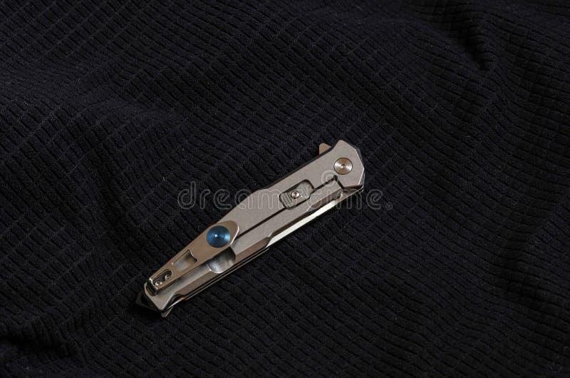 Coltello con una maniglia del metallo nella forma piegata sui tessuti neri fotografia stock