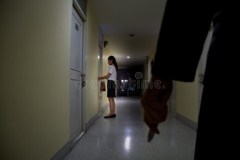 Coltello della tenuta della mano del ladro o del ladro che osserva alla donna di affari che che sblocca porta la notte, fuoco sul immagine stock libera da diritti