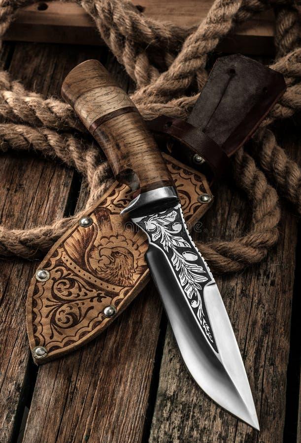 Coltello di caccia con la guaina di cuoio su una tavola di legno fotografie stock