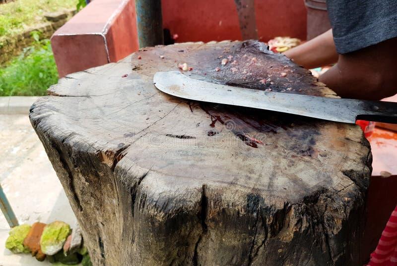 Coltello di macellaio curvo del selettore rotante della carne su una piattaforma di legno immagini stock libere da diritti