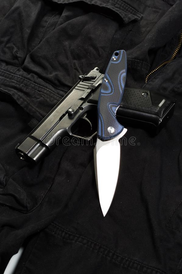 Coltello di tasca sulla pistola Coltello e pistola sui pantaloni neri fotografia stock