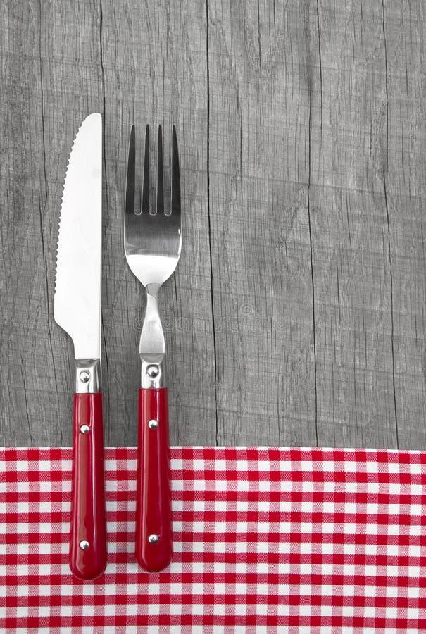 Coltello e forcella su fondo che di legno grigio un rosso chekered immagini stock