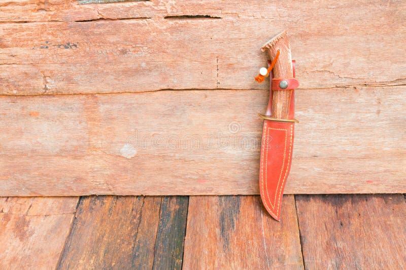 Coltello per l'escursione in cuoio di marrone della guaina su fondo d'annata di legno con lo spazio della copia fotografie stock