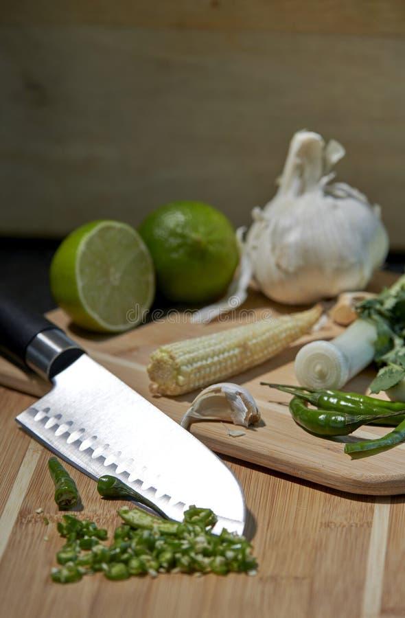 Coltello tagliente ed ingredienti per la frittura o il curry di scalpore con fondo rustico fotografie stock libere da diritti