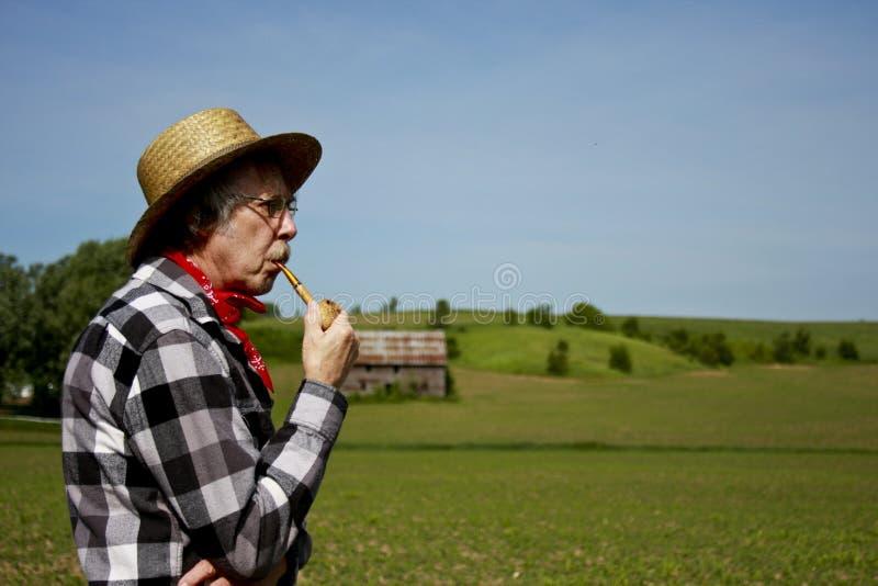 Coltivatore in cappello di paglia con il tubo della pannocchia di granturco immagini stock
