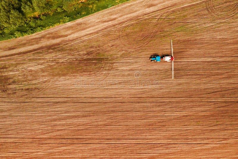 Colture di irrorazione del trattore in campo, vista aerea immagini stock