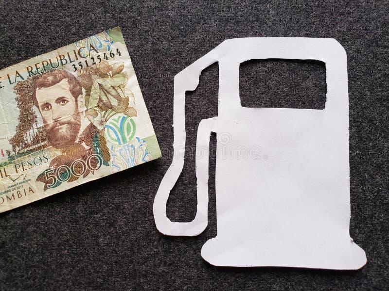 Columbiaans bankbiljet van 5000 peso's en cijfer van benzinepomp in wit stock afbeelding