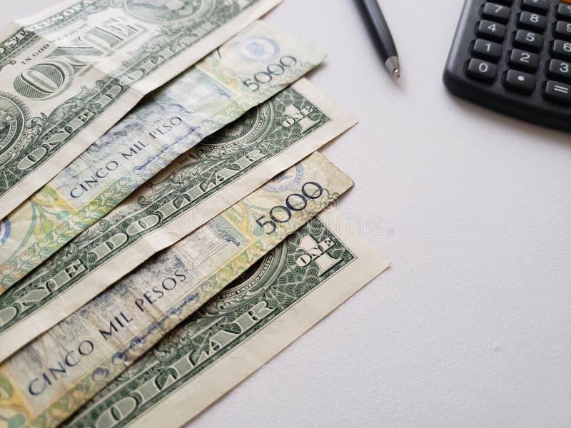 Columbiaanse bankbiljetten, Amerikaanse dollarrekeningen, calculator en zwarte pen op witte achtergrond stock fotografie