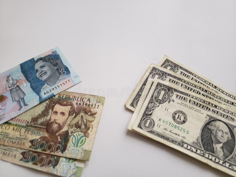 Columbiaanse bankbiljetten en Amerikaanse dollarrekeningen op witte achtergrond stock afbeeldingen