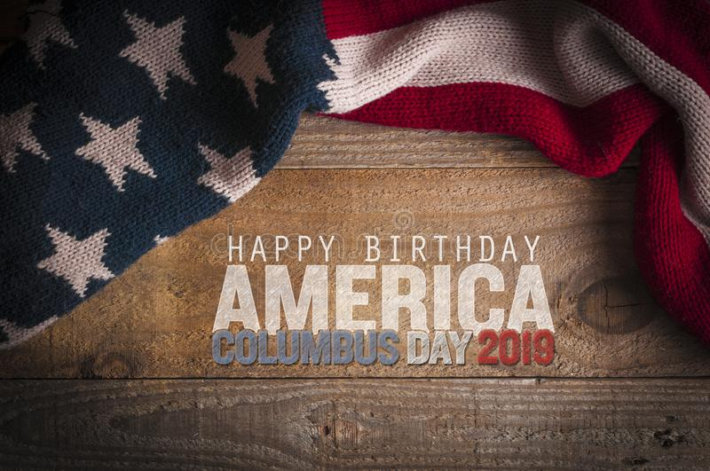 Stars and stripes scarf on a wooden table and an inscription for the Columbus Day celebrations. Columbus day 2019 stock photography