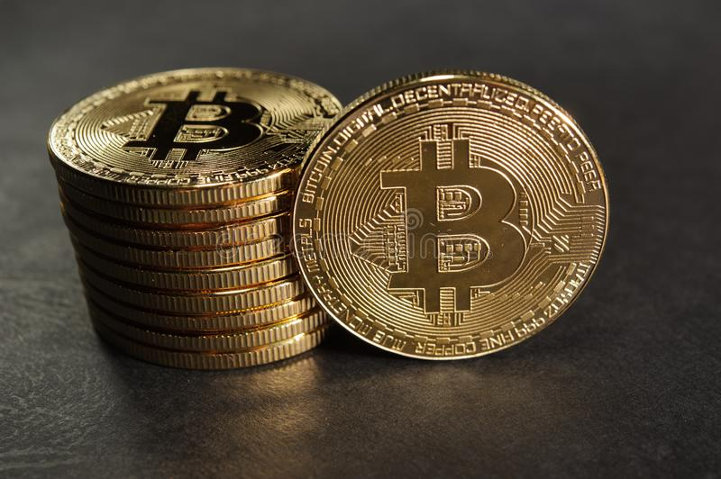 Column of bitcoins with one single coin next to them stock photography