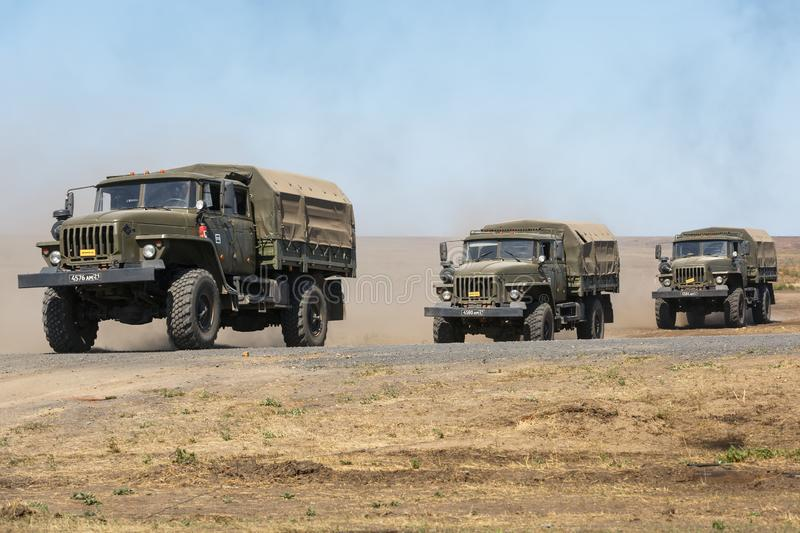 The column consisting of three military trucks Ural carrying soldiers moving across the field stock photo