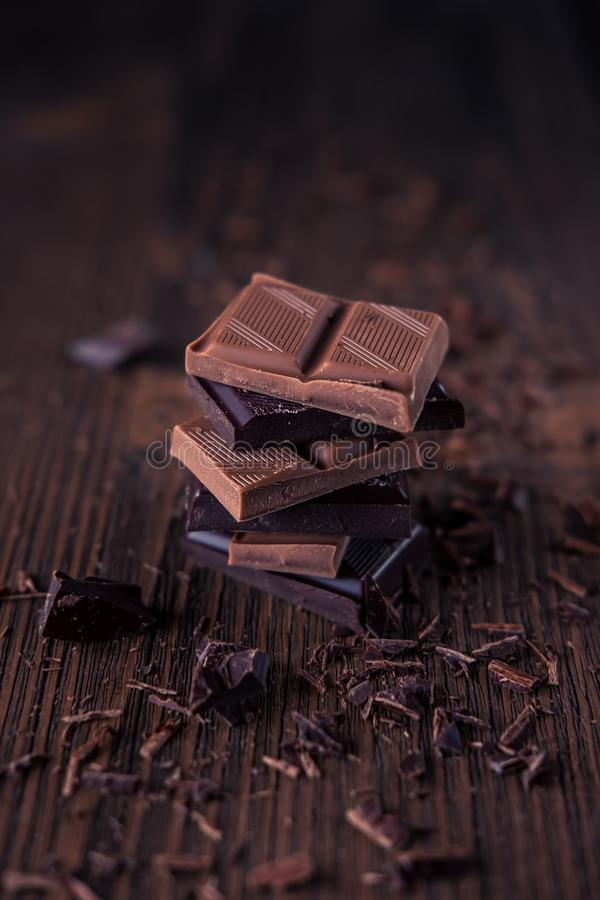Column of dark or bitter or milk chocolate on a wood background stock photography