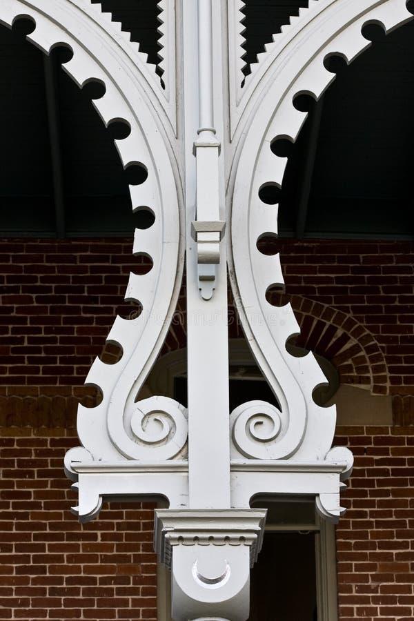 Columna adornada delante de la pared de ladrillo y de la ventana imagenes de archivo