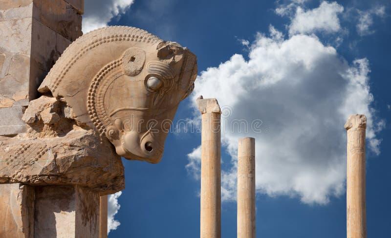 Columna persa con el capital de Bull contra el cielo azul con las nubes mullidas blancas de Persepolis de Shiraz en Irán fotografía de archivo