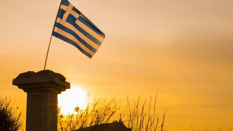 Columna y bandera griegas en la salida del sol, cabo Sounio imagen de archivo