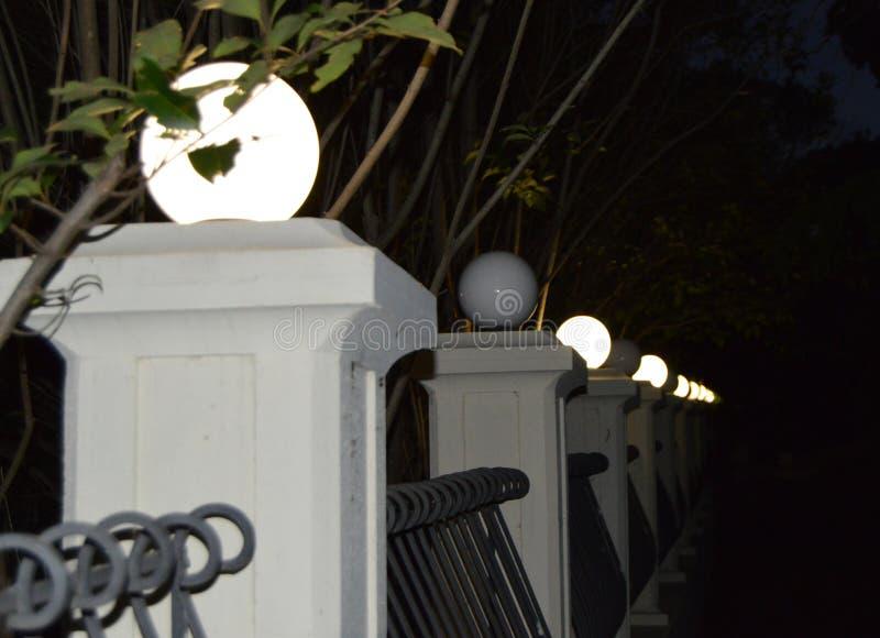 Columnas antiguas con las luces a lo largo de la calzada en el parque en la noche fotos de archivo