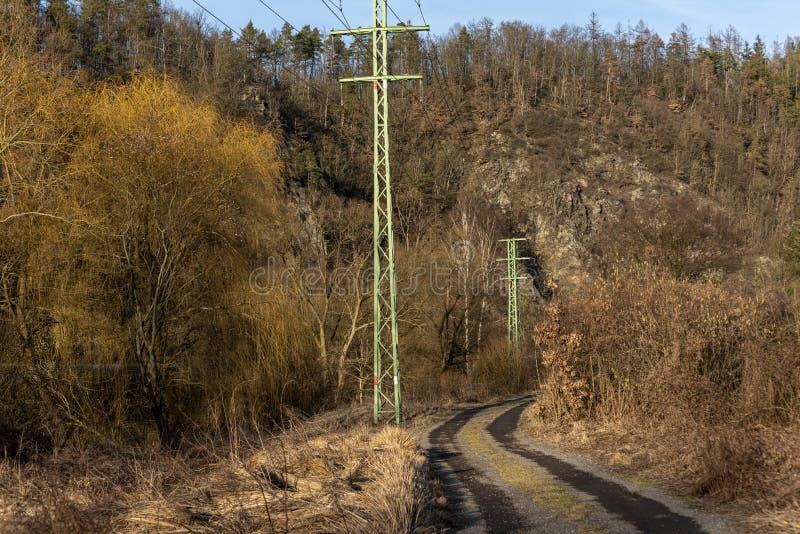 Columnas de líneas eléctricas a lo largo de una trayectoria con el Sazava River Valley imagen de archivo